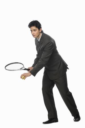 photosindia: Businessman playing tennis