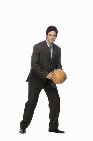 Businessman playing basket ball LANG_EVOIMAGES
