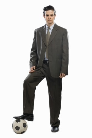 photosindia: Portrait of a businessman with his foot on a soccer ball