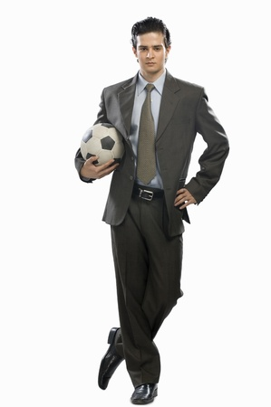sports attire: Portrait of a businessman holding a soccer ball LANG_EVOIMAGES