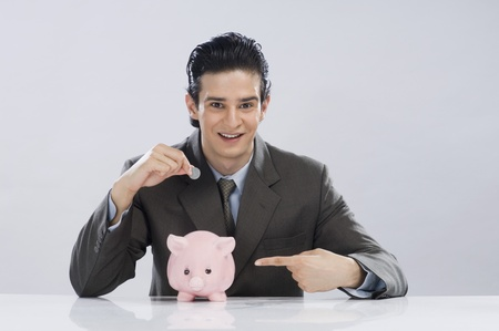 Businessman putting a coin into a piggy bank Stock Photo - 10126118