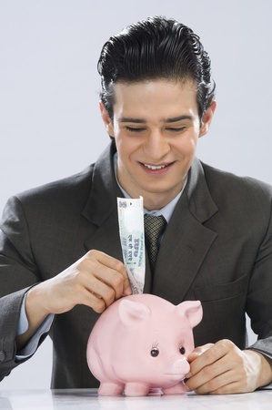 Businessman putting one hundred rupees note in a piggy bank Stock Photo - 10126030