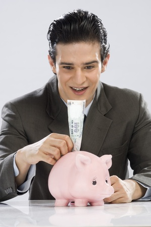 photosindia: Businessman putting one hundred rupees note in a piggy bank