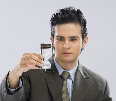 Businessman looking at an hourglass Stock Photo - 10126146