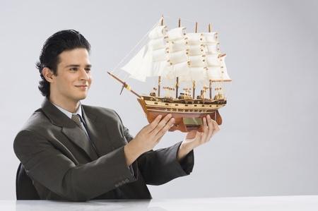 photosindia: Businessman looking at a model ship