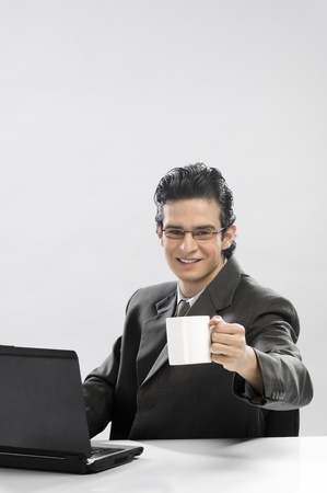 Businessman working at a laptop and holding a coffee cup Stock Photo - 10126088
