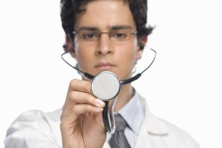photosindia: Male doctor holding a stethoscope