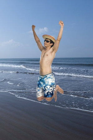 gratified: Man jumping on the beach