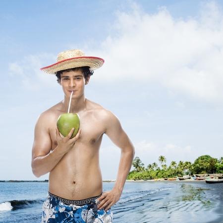 ビーチにココナッツ ミルクを飲む男性