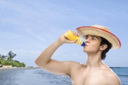Hombre agua de una botella de agua en la playa Foto de archivo - 10126116