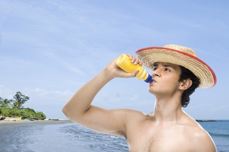 man drinking water: Man drinking water from a water bottle on the beach