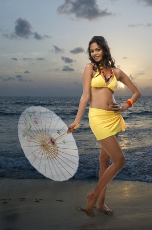 rfbatch15: Portrait of a female fashion model holding a parasol on the beach