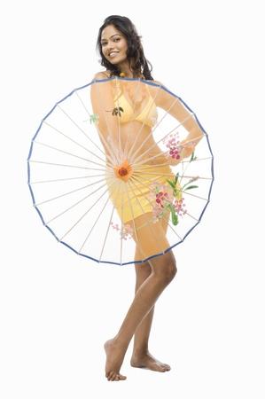 photosindia: Portrait of a female fashion model holding a parasol against white background