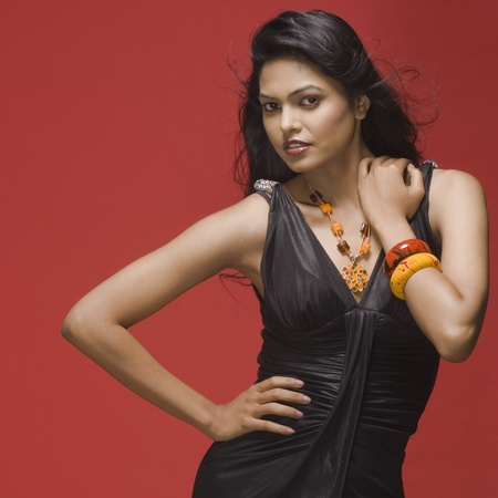 photosindia: Portrait of a female fashion model posing against red background