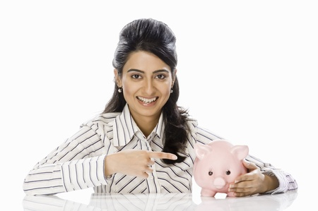 Portrait of a businesswoman pointing towards piggy bank Stock Photo - 10123992