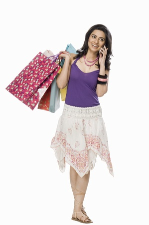 indian subcontinent ethnicity: Woman carrying shopping bags and talking on mobile phone LANG_EVOIMAGES