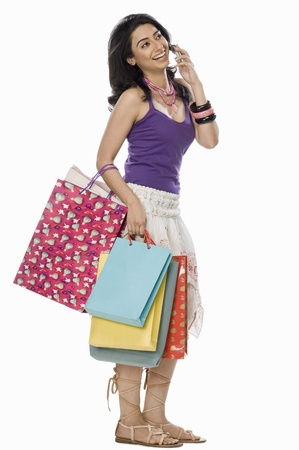 Woman carrying shopping bags and talking on mobile phone Stock Photo - 10124179