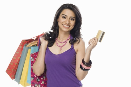 indian subcontinent ethnicity: Portrait of a woman carrying shopping bags and showing a credit card