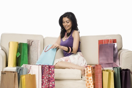 indian subcontinent ethnicity: Woman sitting on a sofa and holding a shopping bag LANG_EVOIMAGES