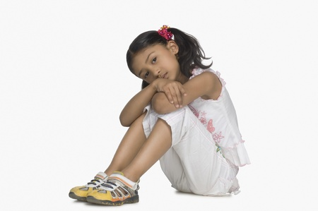 elementary age: Portrait of a girl resting her face on her knees LANG_EVOIMAGES