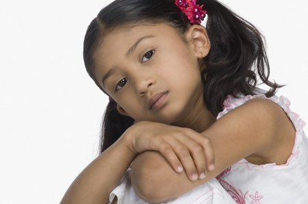 chin on hands: Close-up of a sad girl with her arms crossed