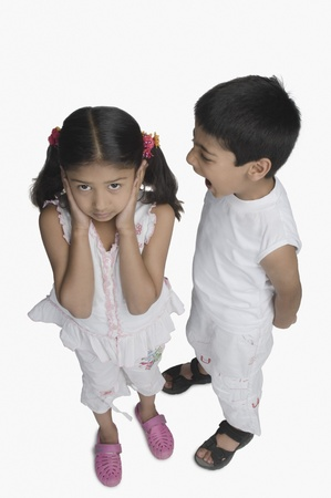 argue kid: Girl covering her ears while her brother talking