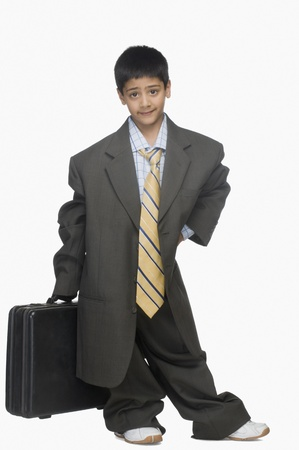 Portrait of a boy wearing oversized suit and holding briefcase