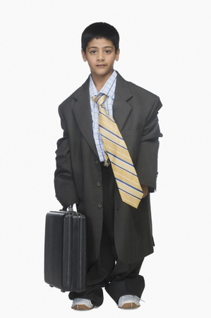 1 boy only: Portrait of a boy wearing oversized suit and holding briefcase