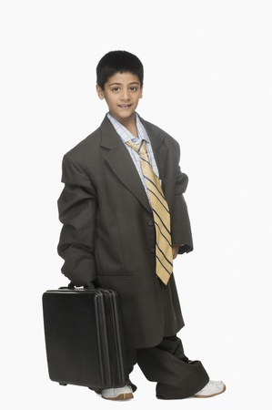 indian boy: Portrait of a boy wearing oversized suit and holding briefcase