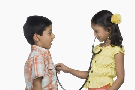 Side profile of a girl examining a boy with a stethoscope Stock Photo - 10125429