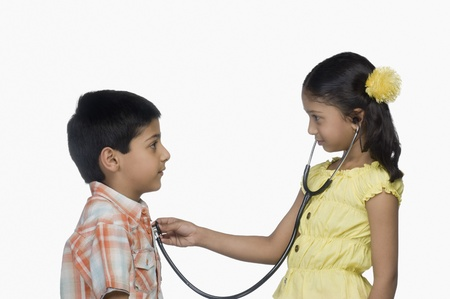 Side profile of a girl examining a boy with a stethoscope Stock Photo - 10124285