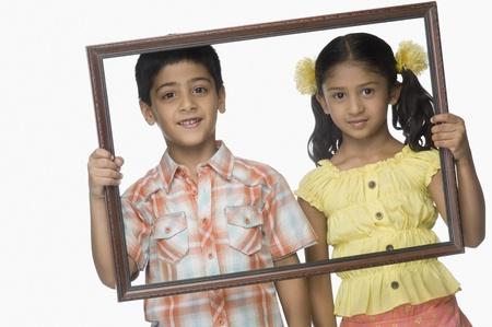 Portret van een meisje en een jongen die een leeg fotolijstje