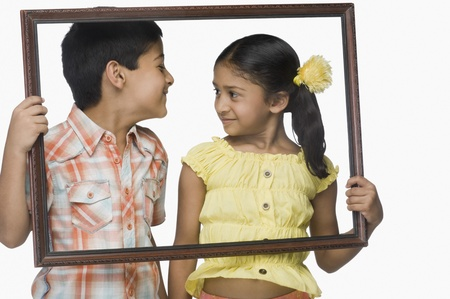 Boy and a girl holding an empty picture frame 版權商用圖片