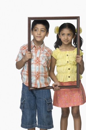 Girl and a boy holding an empty picture frame Stock Photo - 10124869
