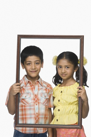 indian subcontinent ethnicity: Portrait of a boy and a girl holding an empty picture frame