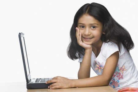 elementary age girl: Portrait of a girl using a laptop