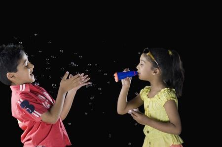 Dívka vyfukování bublin na chlapce Reklamní fotografie - 10124318