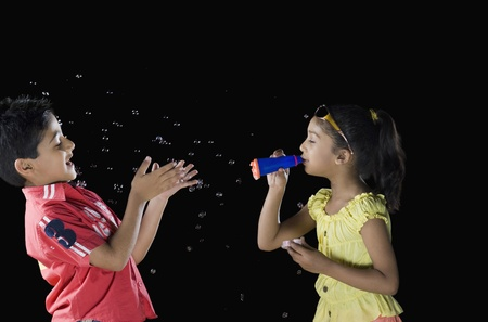 Girl blowing bubbles towards a boy Stock Photo - 10124318