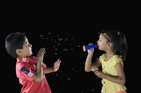 少女少年に向かってシャボン玉を吹く 写真素材
