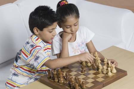 Boy and a girl playing chess Stock Photo
