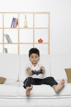 living room sofa: Boy playing handheld video game