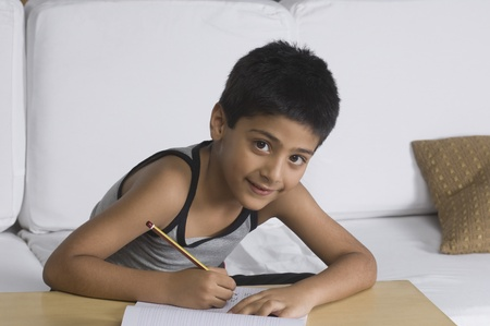 Portrait of a boy sitting on a sofa and writing Stock Photo