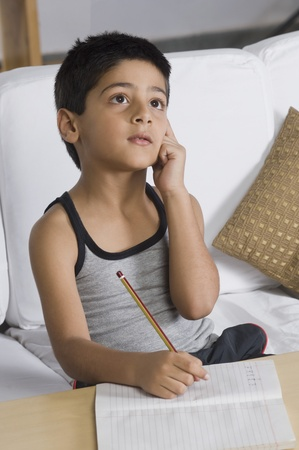 Boy sitting on a sofa and thinking Stock Photo - 10124846