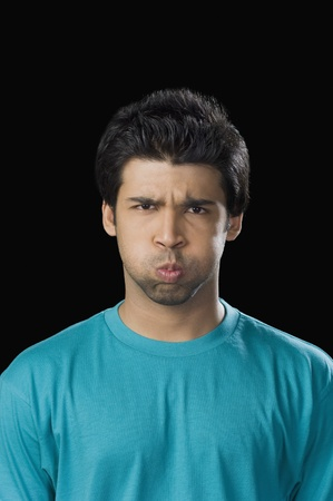 puffed cheeks: Portrait of a man making a face with puffed cheeks LANG_EVOIMAGES