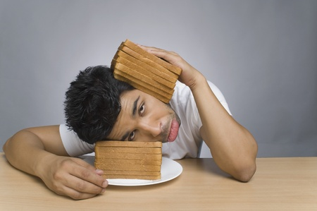 Man looking sad and putting his head between the slices of bread Stock Photo - 10124953