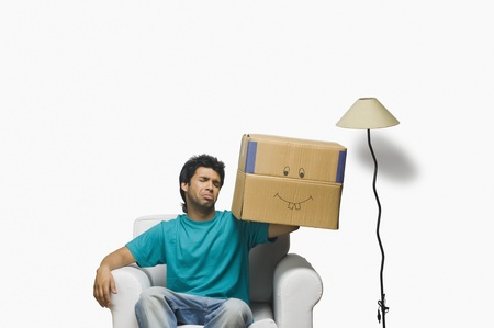 Man holding a cardboard box and making a face Stock Photo - 10124016