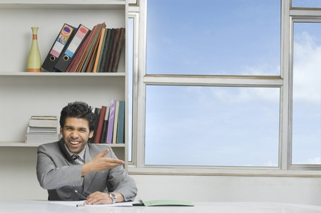 Businessman gesturing and smiling in an office