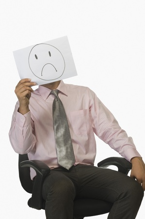 Businessman holding a piece of paper in front of his face with a sad on it Stock Photo - 10124551