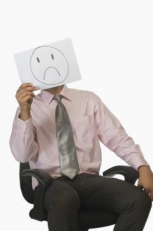 desilusion: Empresario sosteniendo un pedazo de papel delante de su cara con un triste