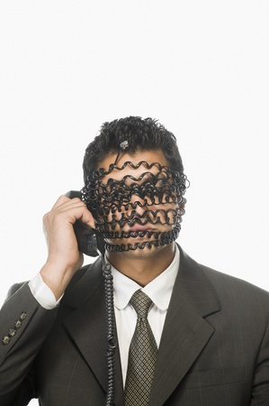 Businessman on the phone with his face covered by phone cord Stock Photo - 10166415